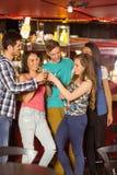 Amigos de sorriso que bebem a cerveja e bebida misturada Fotografia de Stock