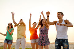 Amigos de sorriso que dançam na praia do verão Fotografia de Stock