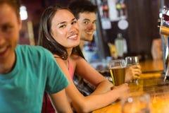 Amigos de sorriso que falam e que bebem a cerveja Fotos de Stock