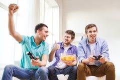 Amigos de sorriso que jogam jogos de vídeo em casa Imagens de Stock Royalty Free