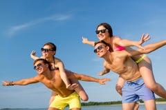 Amigos de sorriso que têm o divertimento na praia do verão Fotografia de Stock Royalty Free