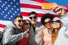 Amigos de sorriso que tomam o selfie com smartphone Fotografia de Stock Royalty Free