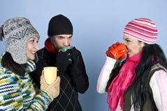 Amigos del grupo que disfrutan de una bebida caliente junto Fotografía de archivo libre de regalías