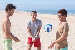 Amigos del grupo que juegan con la bola en la playa Fotos de archivo