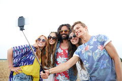 Amigos del hippie con smartphone en el palillo del selfie Foto de archivo
