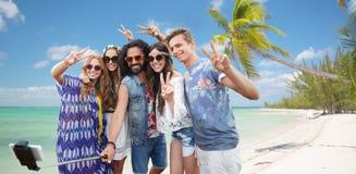 Amigos del hippie con smartphone en el palillo del selfie Fotos de archivo