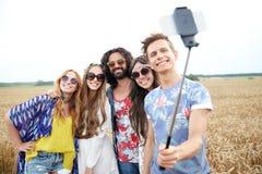 Amigos del hippie con smartphone en el palillo del selfie Fotografía de archivo libre de regalías