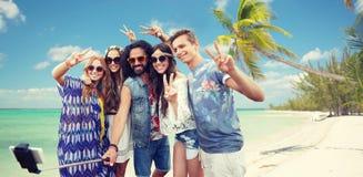 Amigos del hippie con smartphone en el palillo del selfie Imágenes de archivo libres de regalías