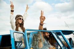Amigos del hippie sobre el coche del minivan que muestra el signo de la paz Foto de archivo
