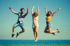 Amigos despreocupados que saltam pela água do oceano do mar Fotografia de Stock Royalty Free