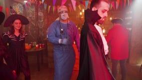 Amigos disfrazados como vampiros, brujas, doctor loco y baile del pirata en un partido de Halloween almacen de metraje de vídeo