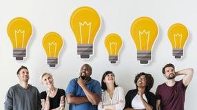 Amigos diversos com conceito criativo dos ícones da ampola Imagens de Stock Royalty Free