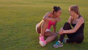 Amigos diversos de las mujeres Muchachas del deporte que hablan al aire libre Mujeres jovenes en hierba metrajes