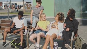 Amigos diversos Lounging no banco na luz do sol vídeos de arquivo