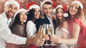 Amigos diversos que tintinean con los vidrios del champán en el ` s Eve del Año Nuevo fotos de archivo libres de regalías