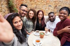Amigos diversos que toman selfies en un patio de moda del café fotos de archivo