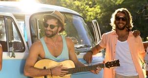 Amigos do moderno que jogam a música e a posição ao lado da camionete filme
