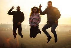 Amigos do salto de Millennials no ar livre em nivelar o por do sol da mola fotos de stock royalty free