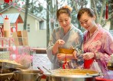 Amigos doces alegres das mulheres que apontam a tenda do alimento Foto de Stock