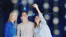 Amigos dos jovens que riem, tomando imagens dse em um clube noturno - um menino e duas mulheres atrativas video estoque