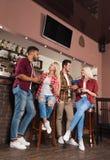 Amigos dos povos que bebem o contador alaranjado de Juice Talking Laughing At Bar, o homem da raça da mistura e o comprimento com Foto de Stock