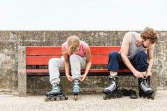Amigos dos povos que põem sobre os patins de rolo exteriores fotos de stock