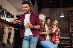 Amigos dos povos que usam o telefone esperto da pilha, contador alaranjado bebendo da barra de Juice Talking Laughing Sitting At, Foto de Stock Royalty Free