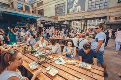 Amigos e fmilies que têm o jantar em torno das tabelas exteriores durante o partido do verão do festival do alimento da rua Imagens de Stock Royalty Free