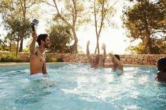 Amigos el las vacaciones que toman Selfie en de la piscina al aire libre Foto de archivo libre de regalías