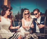 Amigos elegantes en un yate de lujo Fotos de archivo libres de regalías
