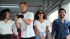 Amigos elegantes felices en ropa de moda casual en el aparcamiento almacen de video