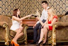 Amigos elegantes felizes que têm uma bebida Imagens de Stock Royalty Free
