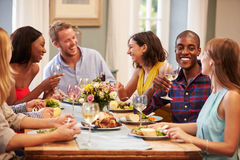 Amigos em casa que sentam-se em torno da tabela para o partido de jantar foto de stock