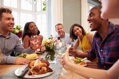 Amigos em casa que sentam-se em torno da tabela para o partido de jantar imagens de stock royalty free
