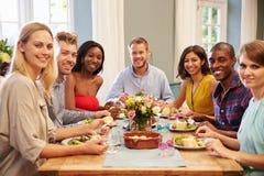 Amigos em casa que sentam-se em torno da tabela para o partido de jantar fotos de stock royalty free