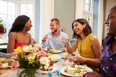 Amigos em casa que sentam-se em torno da tabela para o partido de jantar fotografia de stock