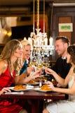 Amigos em vidros muito bons de um clink do restaurante Imagens de Stock
