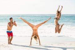 Amigos emocionados hermosos que saltan en la playa Fotos de archivo