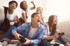 Amigos emocionados que juegan a los videojuegos en casa fotografía de archivo libre de regalías