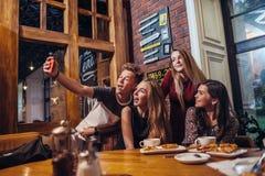 Amigos emocionados que toman el selfie con el smartphone que se sienta en la tabla que tiene noche hacia fuera Imagen de archivo libre de regalías