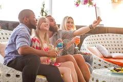 Amigos emocionais felizes que tomam imagens na sala de estar Fotos de Stock Royalty Free