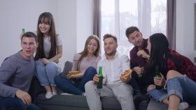 Amigos emocionales de las fans que miran campeonato de los deportes en la televisión y comer la pizza y beber la cerveza de las b almacen de metraje de vídeo