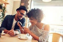 Amigos en café usando el teléfono móvil Fotos de archivo