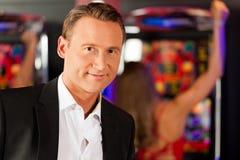 Amigos en casino en la máquina tragaperras fotografía de archivo libre de regalías