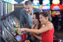 Amigos en casino en la máquina tragaperras foto de archivo