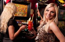 Amigos en casino en una máquina tragaperras imagen de archivo