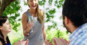 Amigos en el almuerzo al aire libre que aplauden para la mujer almacen de video