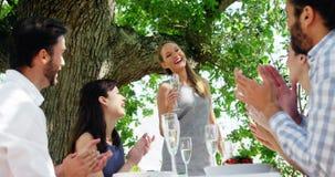 Amigos en el almuerzo al aire libre que aplauden para la mujer almacen de metraje de vídeo