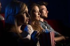 Amigos en el cine que miran una película Fotografía de archivo