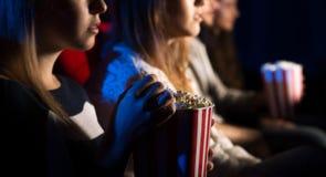 Amigos en el cine que miran una película Fotos de archivo libres de regalías